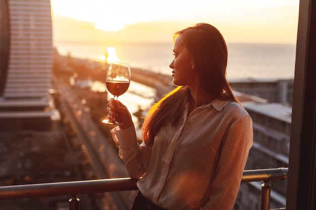 Young person is relaxing and drinking a glass of red wine on the balcony at sunset in the evening Premium Photo