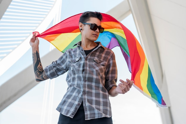 Young person keeping fluttering rainbow flag Free Photo