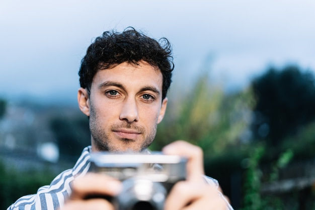 Young photographer is taking a picture with a retro camera Premium Photo