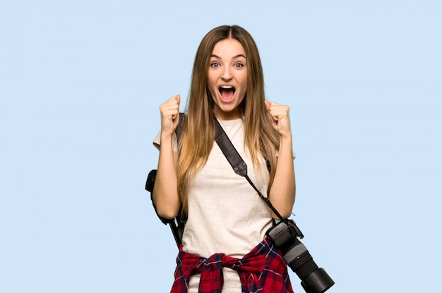 Young photographer woman celebrating a victory in winner position on isolated blue background Premium Photo