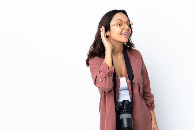 耳に手を置いて何かを聞いている孤立した白い壁の上の若い写真家の女性 Premium写真
