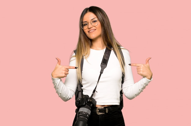 Young photographer woman proud and self-satisfied in love yourself concept on isolated pink background Premium Photo