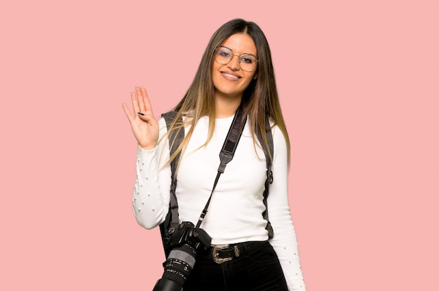 Young photographer woman saluting with hand with happy expression on isolated pink background Premium Photo