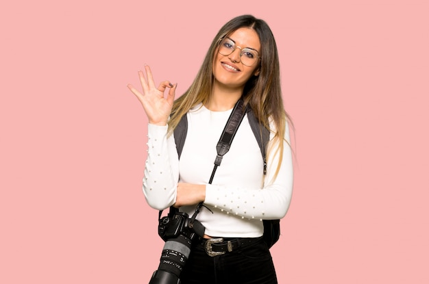 Young photographer woman showing an ok sign with fingers on isolated pink wall Premium Photo