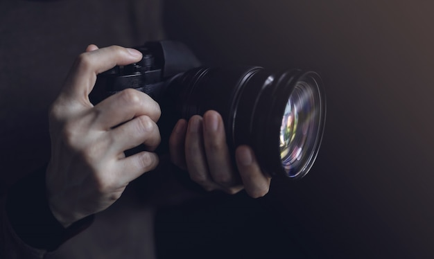 Young photographer woman using camera to taking photo. dark tone. selective focus on hand Premium Photo