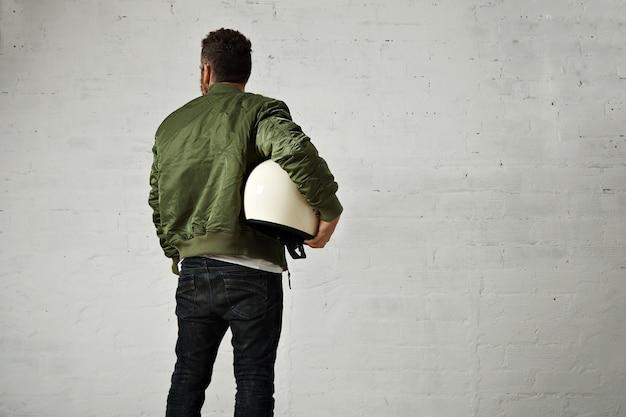ジーンズ、緑のボンバージャケット、白い壁の後ろから彼の腕の肖像画の下に丸い白いヘルメットの若いパイロット 無料写真