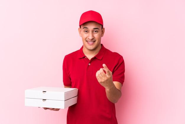 Молодой латинский человек доставки пиццы изолирован, указывая пальцем на вас, как будто приглашая подойти ближе. Premium Фотографии
