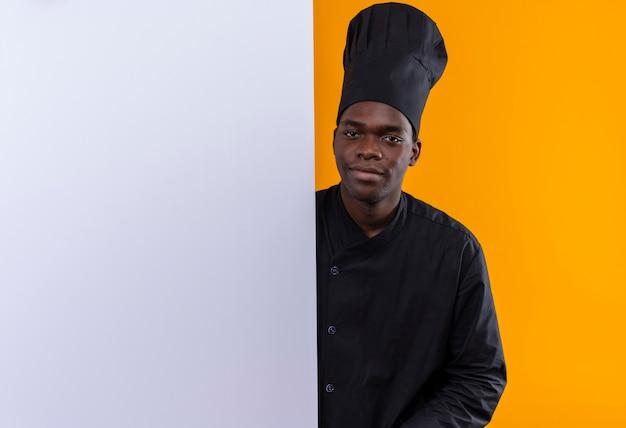 コピースペースとオレンジ色のスペースに分離された白い壁の後ろに立っているシェフの制服を着た若い喜んでアフリカ系アメリカ人の料理人 無料写真
