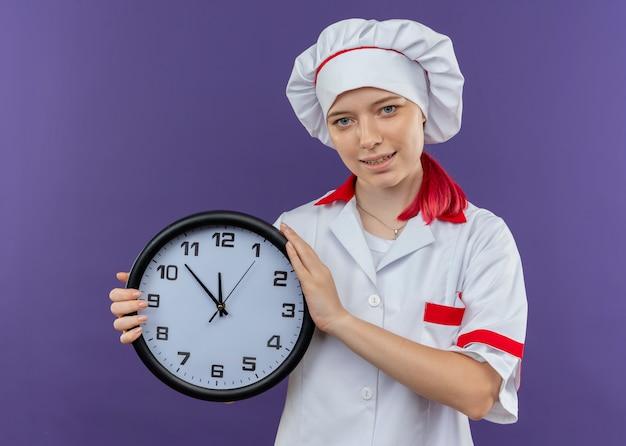 Il giovane chef femmina bionda felice in uniforme da chef tiene l'orologio e sembra isolato sulla parete viola Foto Gratuite