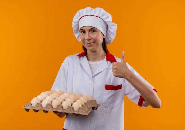 Young pleased caucasian cook girl in chef uniform holds batch of eggs and thumbs up isolated on orange space with copy space Free Photo