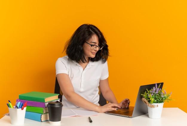 眼鏡をかけている若い喜んでかなり白人の女子高生は、学校のツールの仕事で机に座って、コピースペースでオレンジ色のスペースに分離されたラップトップを見て 無料写真