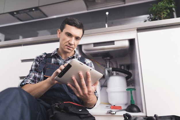 Young plumber sits near the sink with tablet. Premium Photo