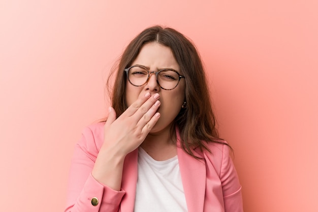 Young plus size business caucasian woman yawning showingtired gesture covering mouth with him hand. Premium Photo