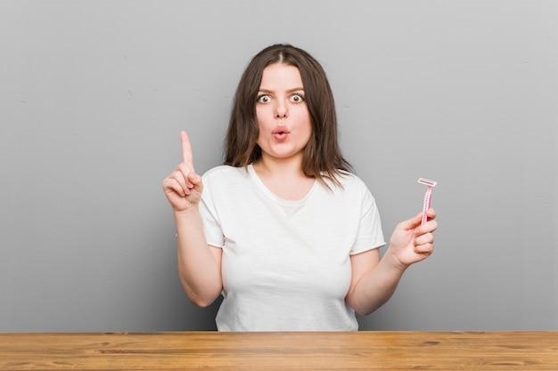 いくつかの素晴らしいアイデア、創造性の概念を持つかみそりの刃を持つ若いプラスサイズの曲線の女性。 Premium写真