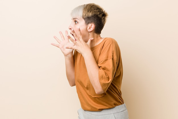 Young plus size woman with short hair shouts loud, keeps eyes opened and hands tense. Premium Photo