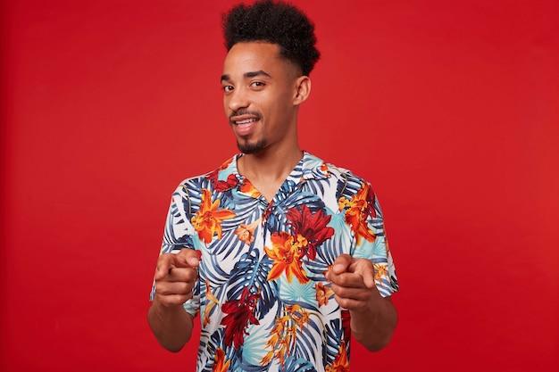 Молодой позитивный афроамериканец одет в гавайскую рубашку, смотрит в камеру и широко улыбается, показывает пальцами на камеру и говорит, что «ты крут» стоит на красном фоне. Бесплатные Фотографии