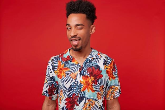 Молодой позитивный афроамериканец в гавайской рубашке, смотрит в камеру и подмигивает, стоит на красном фоне. Бесплатные Фотографии
