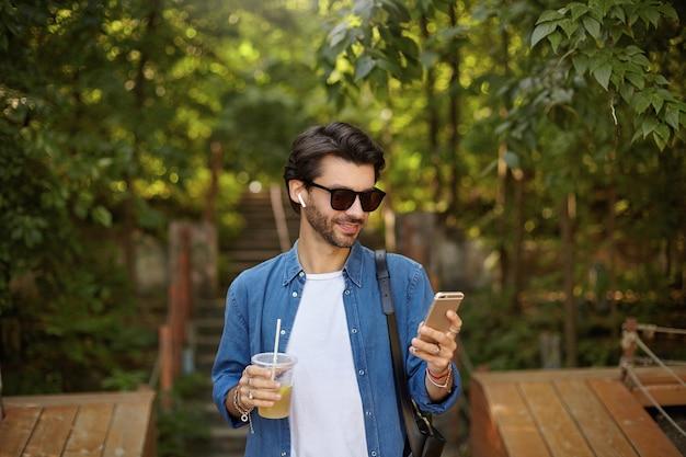 晴れた暖かい日に都市公園を歩いて、彼の携帯電話でメッセージをチェックし、ジュースを飲むひげを持つ若いポジティブハンサムな男性 無料写真