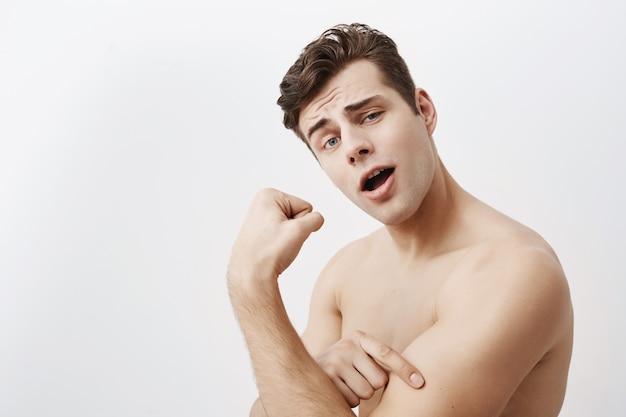 黒い髪と青い目を持つ若い肯定的な筋肉男は、分離されたジムでトレーニング後の上腕二頭筋を示しています。ハンサムな白人男性は強さを誇り、強い男の手を示しています 無料写真