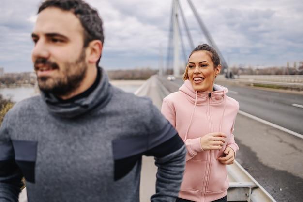 曇りの天候で橋の上を走っているスポーツウェアの若い肯定的な笑顔の異性愛の友人。 Premium写真