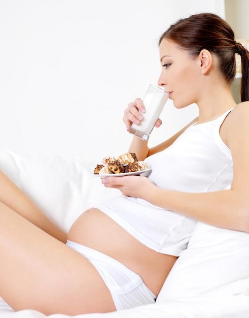 若い妊婦は家でケーキsittinhと牛乳を飲む 無料写真