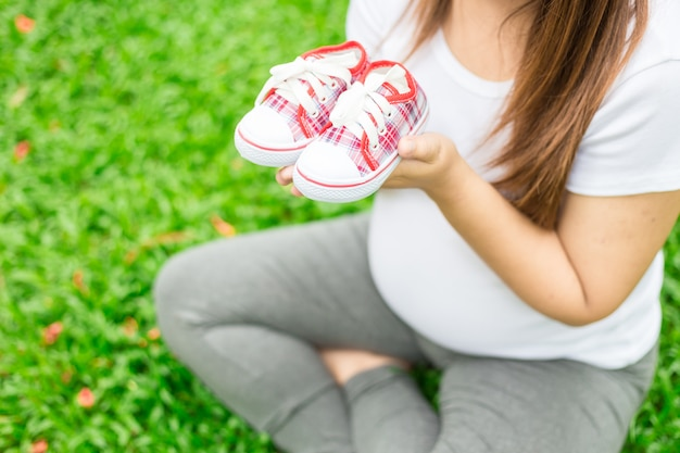 Young pregnant woman holding baby shoes to her belly Premium Photo