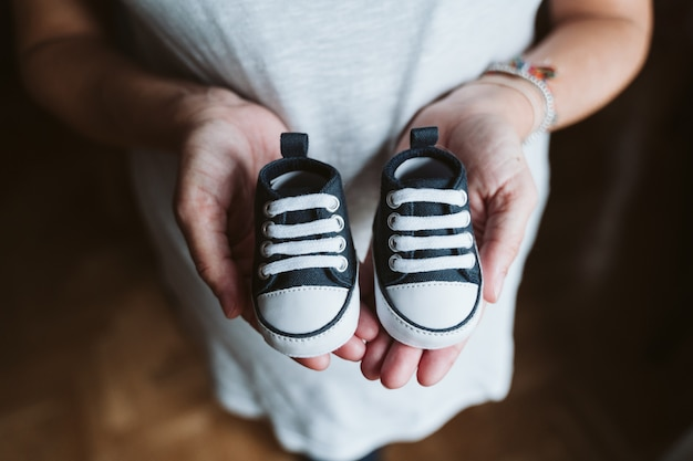 Young pregnant woman at home holding baby shoes Premium Photo