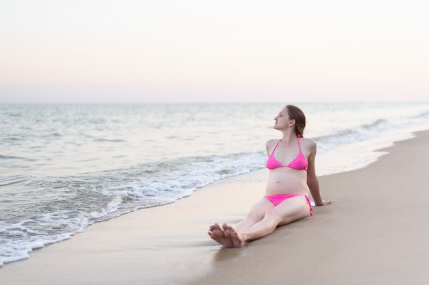Young pregnant woman is sitting on the sea shore, enjoying nature. deserted beach, pre sunset time Premium Photo
