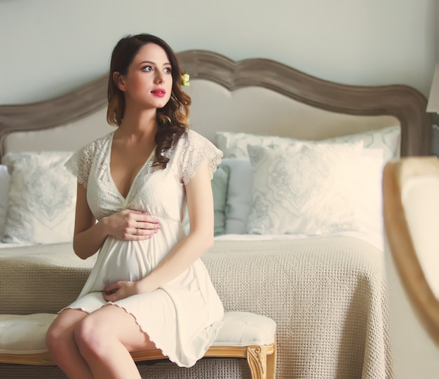 Young pregnant woman in white dress sitting Premium Photo