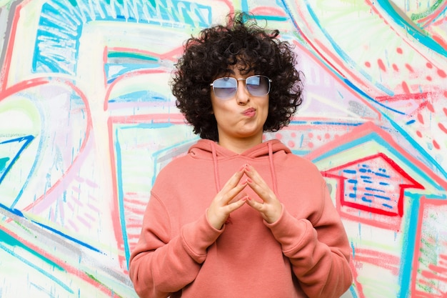 Young pretty afro woman scheming and conspiring, thinking devious tricks and cheats, cunning and betraying  graffiti wall Premium Photo