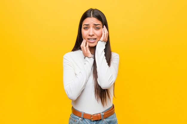 Young pretty arab woman against a yellow background whining and crying disconsolately. Premium Photo