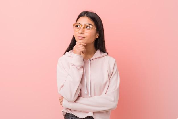 Молодая милая арабская женщина нося взгляд вскользь спорта смотря косой с сомнительным и скептическим выражением. Premium Фотографии