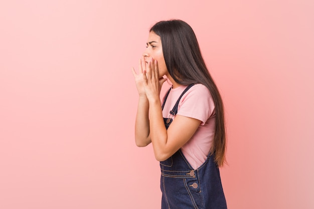 Young pretty arab woman wearing a jeans dungaree shouts loud, keeps eyes opened and hands tense. Premium Photo