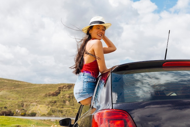Young pretty asian woman loving life out of car window Free Photo