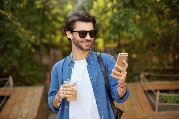 緑豊かな街の庭を歩いて、レモネードを飲み、携帯電話を手に持って、画面を見て、元気に笑って、黒髪の若いきれいなひげを生やした男性 無料写真
