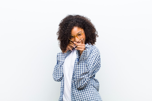 Young pretty black woman with a smart phone  white wall Premium Photo