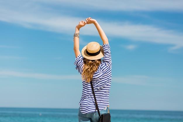Giovane bella bionda abbronzata giovane donna in piedi sulla spiaggia vicino al mare indietro in attesa e sognare Foto Gratuite
