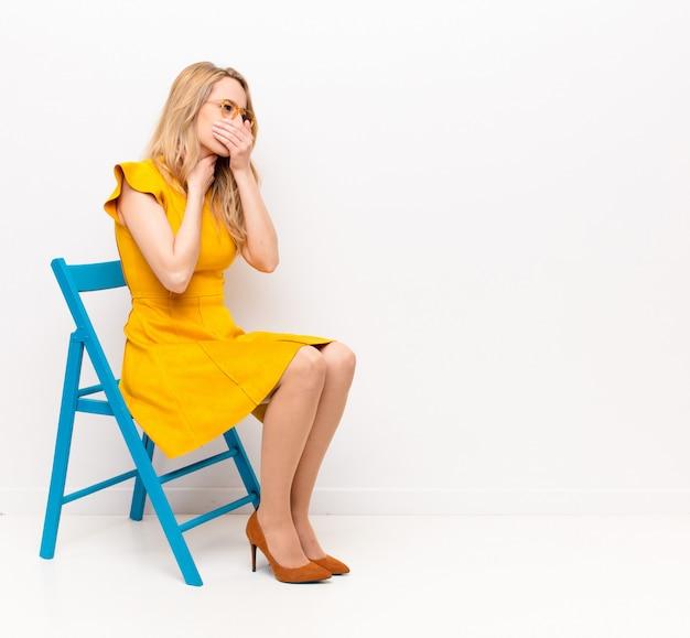 Молодая симпатичная блондинка чувствует себя плохо, с симптомами гриппа и болью в горле, кашляет, прикрыв ртом плоскую цветную стену Premium Фотографии