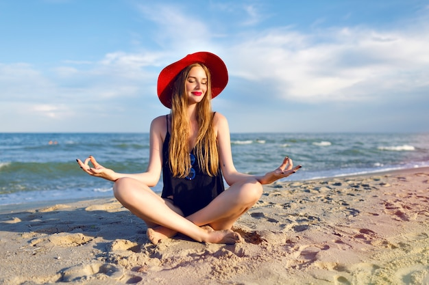 Young pretty blonde woman wearing black bikini, slim body, enjoy vacation and having fun on the beach, long blonde hairs, sunglasses and straw hat. vacation on bali. Free Photo