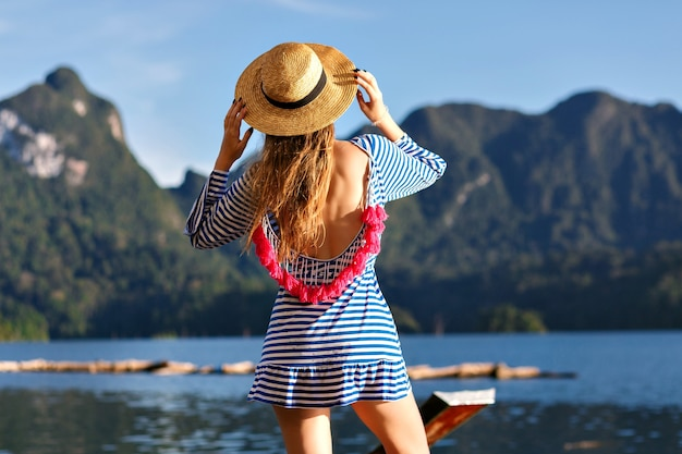 ヴィンテージの帽子と明るくセクシーなトレンディなドレスを身に着けている長い髪の若いきれいなブロンドの女性は、山や湖に見え、彼女の手を見せて、素晴らしい夏の冒険をします。 無料写真