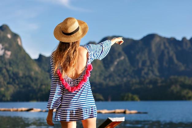 Молодая симпатичная блондинка с длинными волосами, в винтажной шляпе и ярком сексуальном модном платье смотрит на горы и озеро, показывает свою руку, удивительные летние приключения. Бесплатные Фотографии
