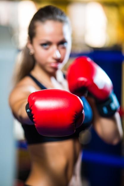リングの上に立って、サンドバッグで運動をしている若いかわいいボクサーの女性 無料写真