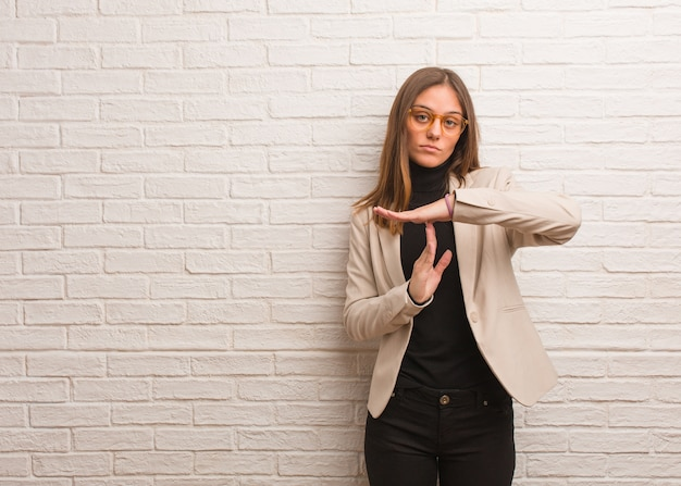 Молодая красивая деловая женщина-предприниматель делает жест тайм-аута Premium Фотографии
