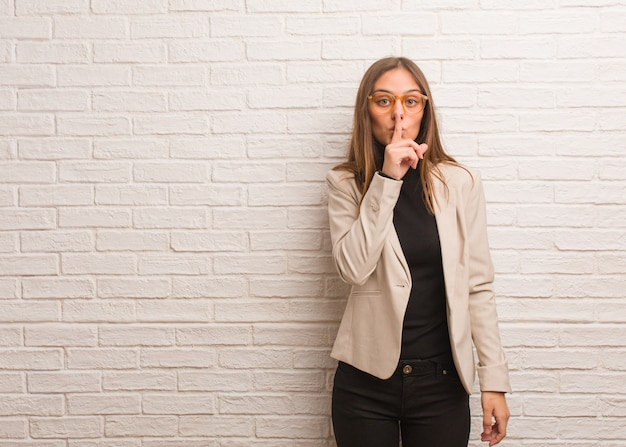 Young pretty business entrepreneur woman keeping a secret or asking for silence Premium Photo