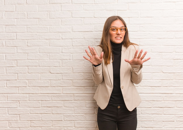 Young pretty business entrepreneur woman rejecting something doing a gesture of disgust Premium Photo