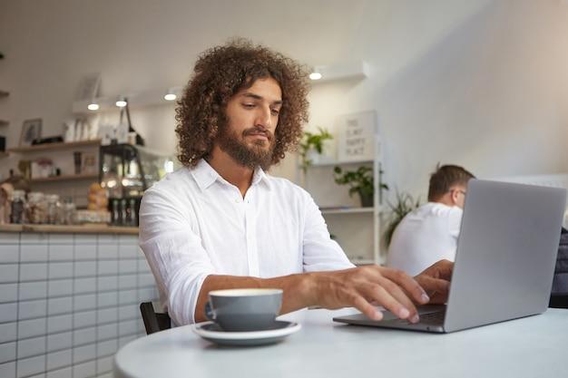 カフェのテーブルに座って、彼のノートブックでリモートで作業し、お茶を飲みながら、ひげと茶色の巻き毛の白いシャツを着た若いかわいいビジネスマン 無料写真