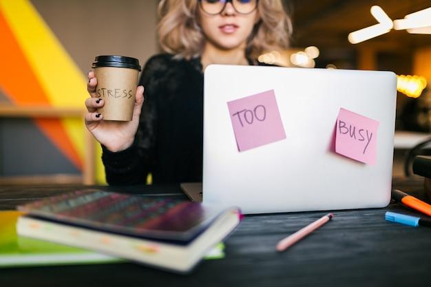 コワーキングオフィス、クローズアップビュー、同意、疲れて、コーヒーカップを保持しているラップトップに取り組んでいるテーブルに座っている若いかなり忙しい女性 無料写真