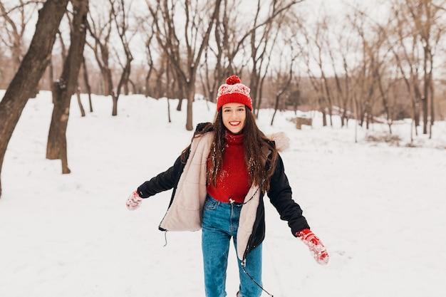 赤いミトンと帽子をかぶった若いかなり率直な笑顔の幸せな女性は、暖かい服を着て雪の中で公園で遊んで歩いて、楽しんで 無料写真