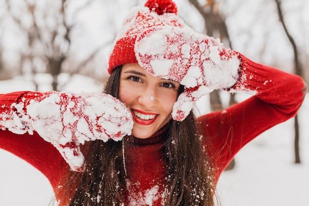 Giovane donna felice sorridente abbastanza candida in guanti rossi e cappello che indossa un maglione lavorato a maglia a piedi giocando nel parco nella neve, vestiti caldi, divertendosi Foto Gratuite
