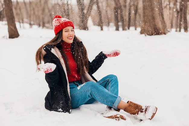 Young pretty candid smiling happy woman in red mittens and knitted hat wearing black coat walking playing in park in snow, warm clothes, having fun Free Photo